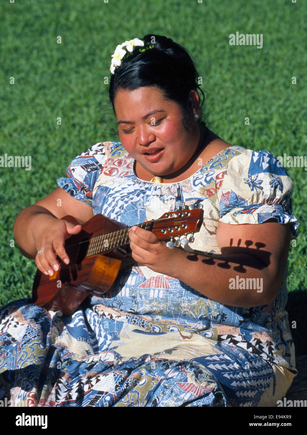 A young Hawaiian woman in Honolulu, Hawaii, USA, sings and strums an eight-string ukelele outdoors in the bright Stock Photo