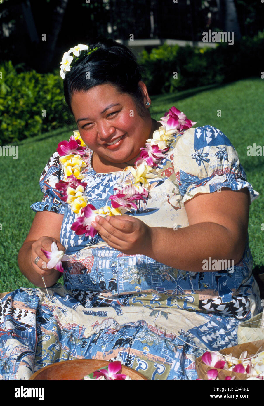A smiling Hawaiian woman in Honolulu, Hawaii, USA, makes traditional leis with plumeria (frangipani) flowers outdoors - Stock Image
