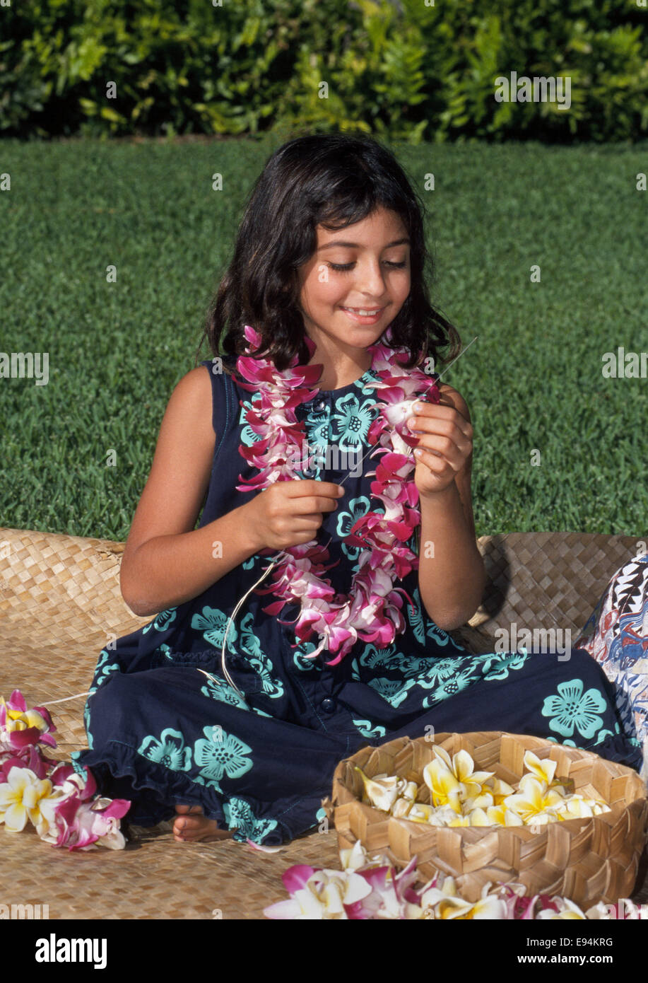 An 8-year-old Hawaiian girl uses a long needle to string leis of orchid and plumeria flowers outdoors in Honolulu, - Stock Image