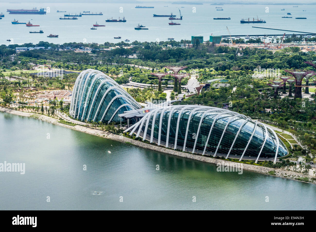 Flower Dome and Cloud Forest dome in Gardens by the Bay, singapore with many ships at anchor in the background. - Stock Image
