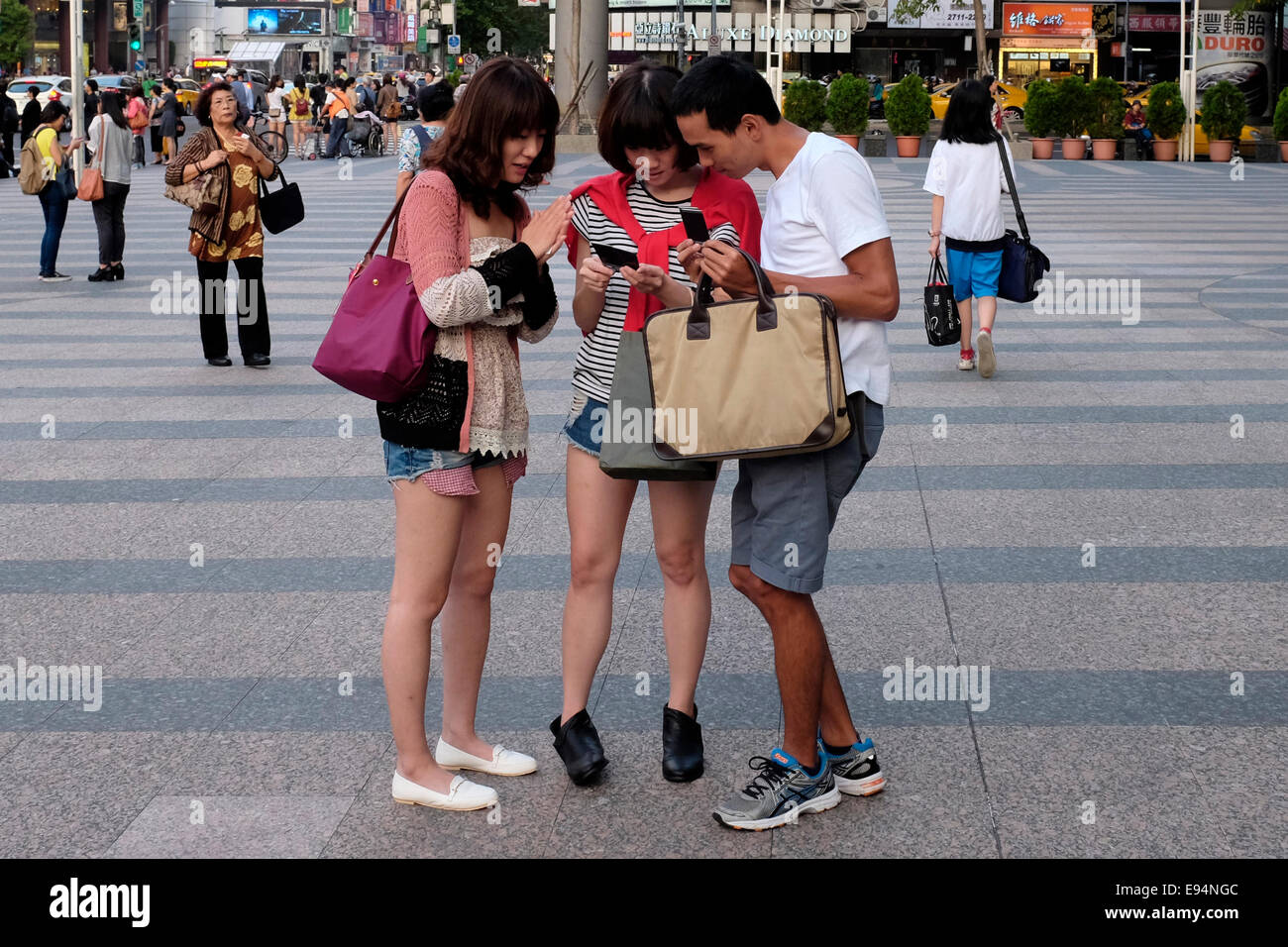 Sharing a cell phone moment in Taipei, Taiwan - Stock Image