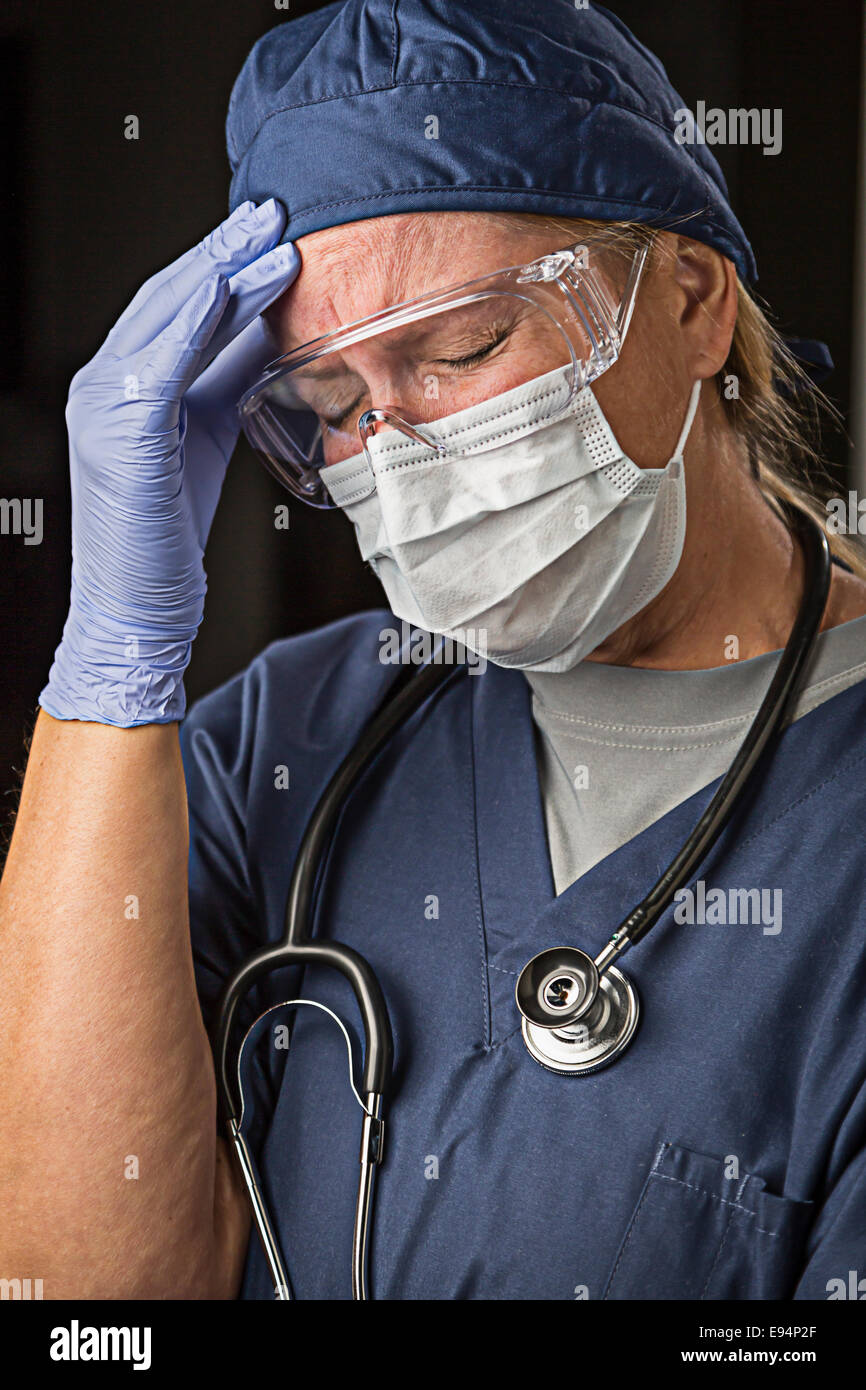 Grimacing Female Doctor or Nurse Wearing Protective Facial Wear and Surgical Gloves. - Stock Image