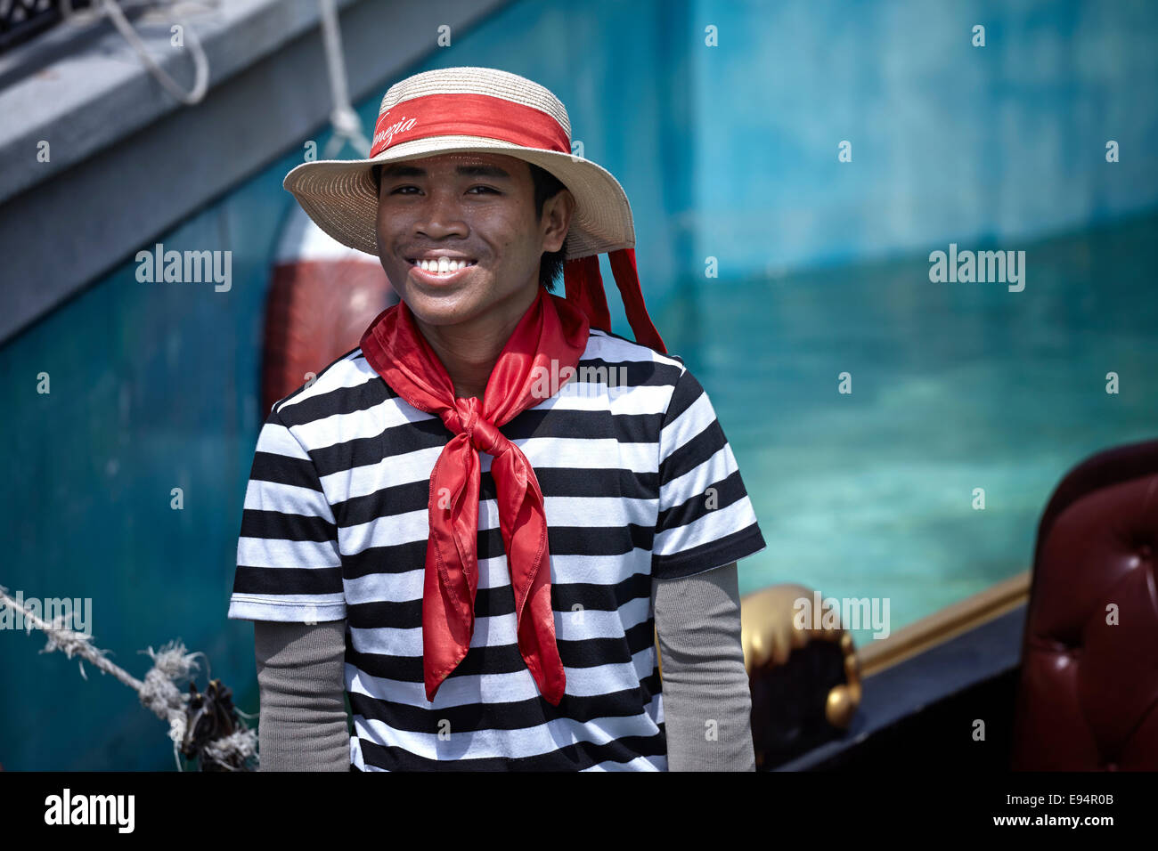 Smiling Gondolier in traditional attire. - Stock Image