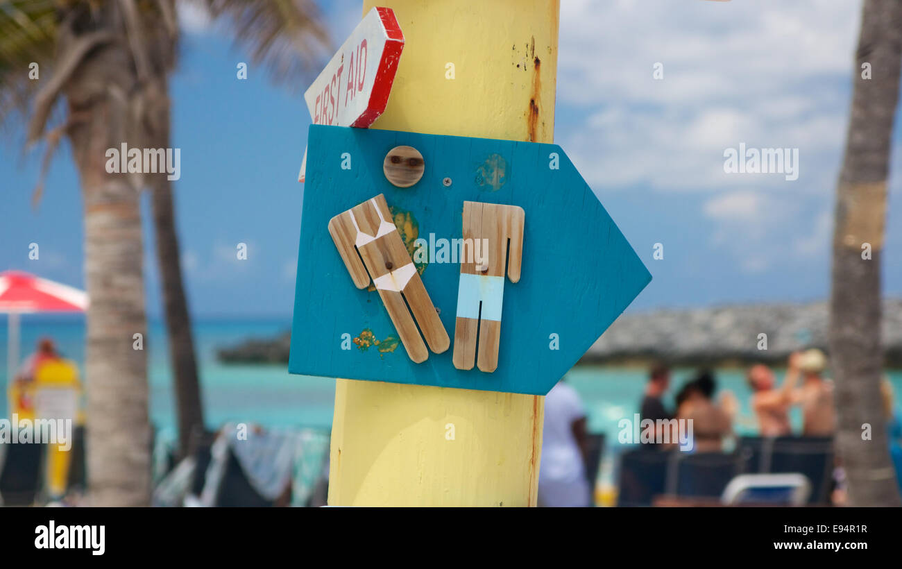 Damaged wooden sign on a crooked signpost pointing towards the restrooms at a Caribbean beach party. - Stock Image
