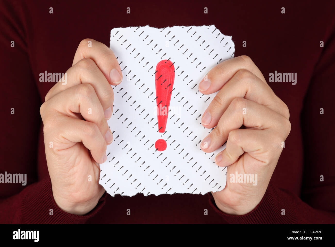 Piece of paper with red Exclamation mark in the woman's hands. - Stock Image