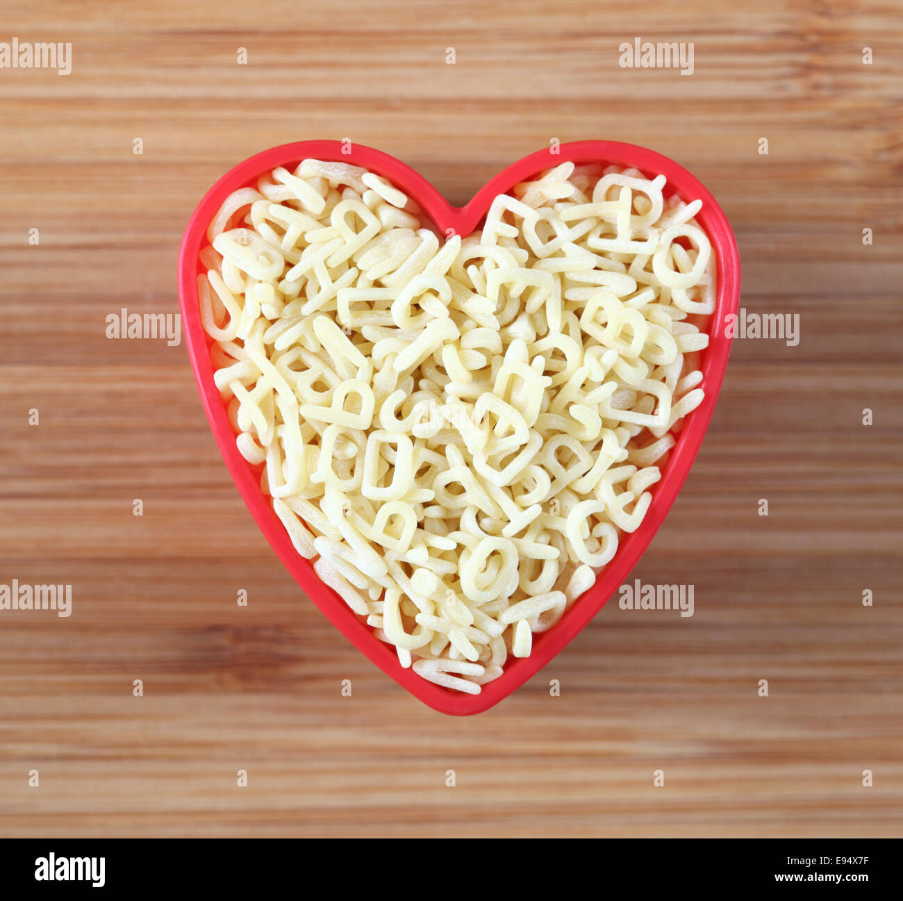 Raw alphabet soup pasta in a heart bowl. Close-up. - Stock Image