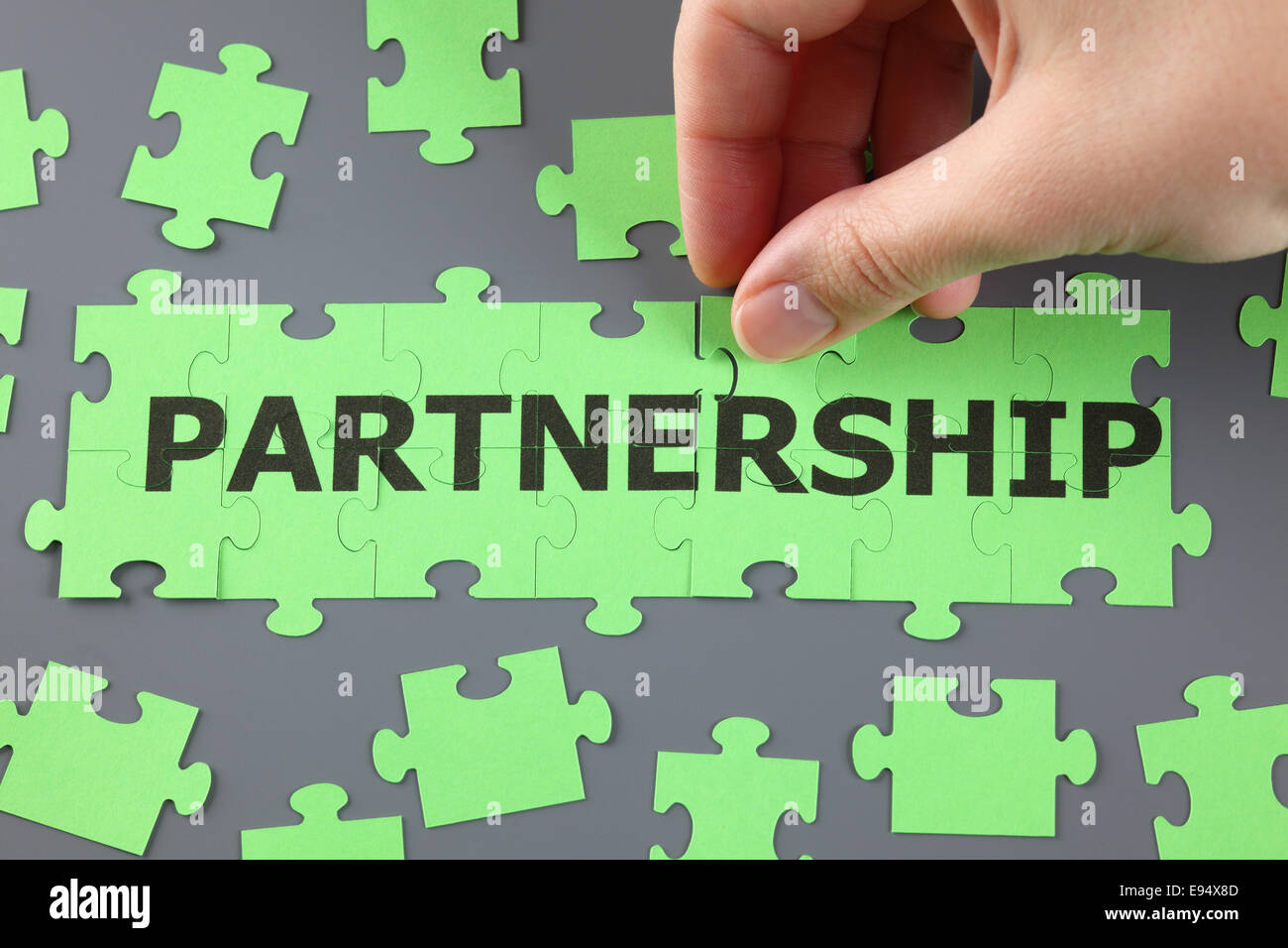 Woman's hand completing  jigsaw puzzle with word 'Partnership'. - Stock Image