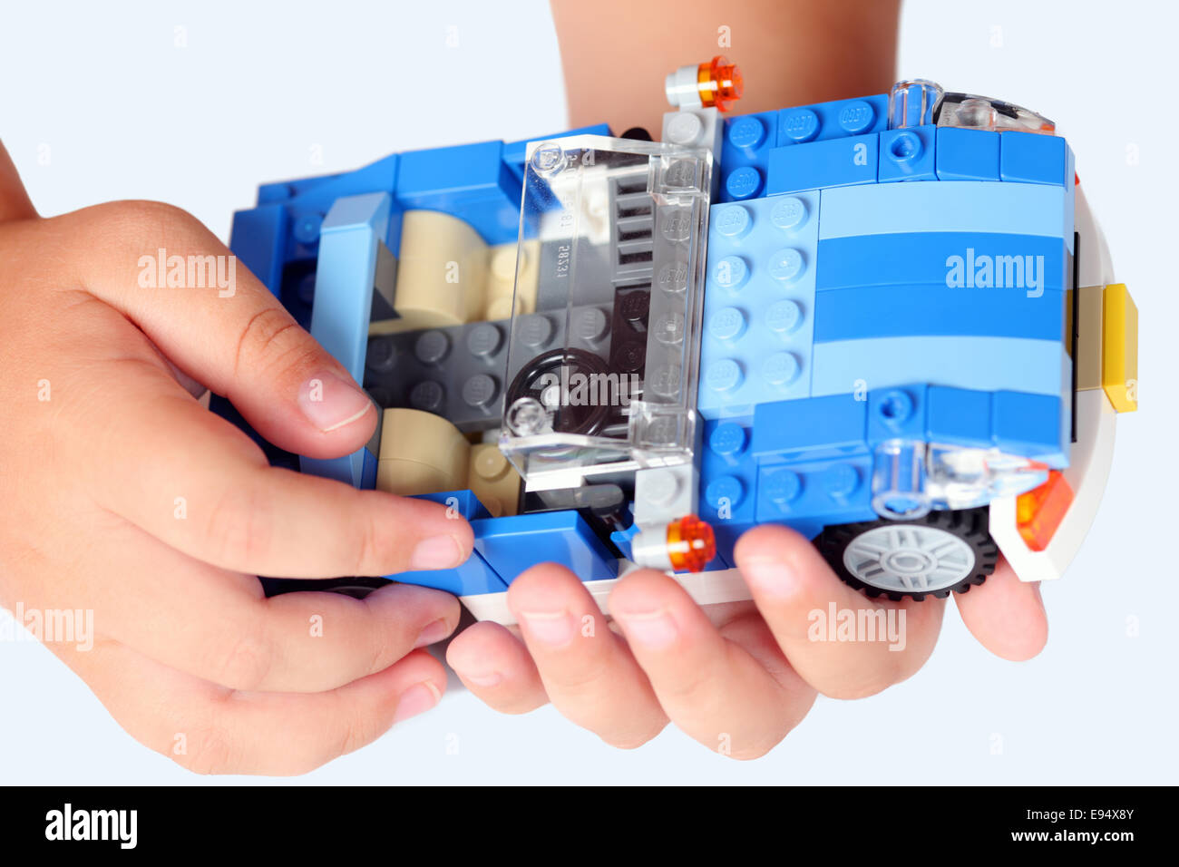 Tambov, Russian Federation - August 10, 2012 LEGO car from Creator set 'Blue Roadster' in child's hands. - Stock Image