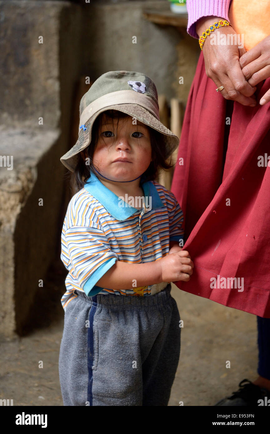 Little boy clinging to the coat-tails of his mother, Chuquis, Huanuco Province, Peru - Stock Image