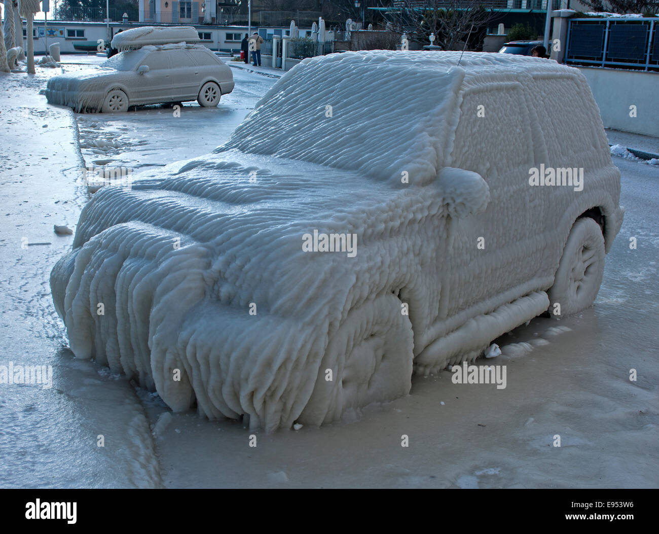 Car with a thick layer of ice parked in a street on Lake Geneva, Versoix, Canton of Geneva, Switzerland - Stock Image
