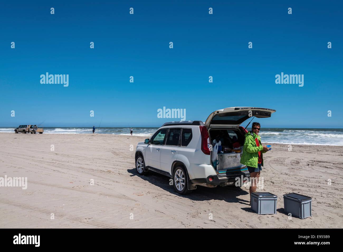 Tourist standing next to an SUV on the Namibian coast near Swakopmund, Erongo Region, Namibia - Stock Image