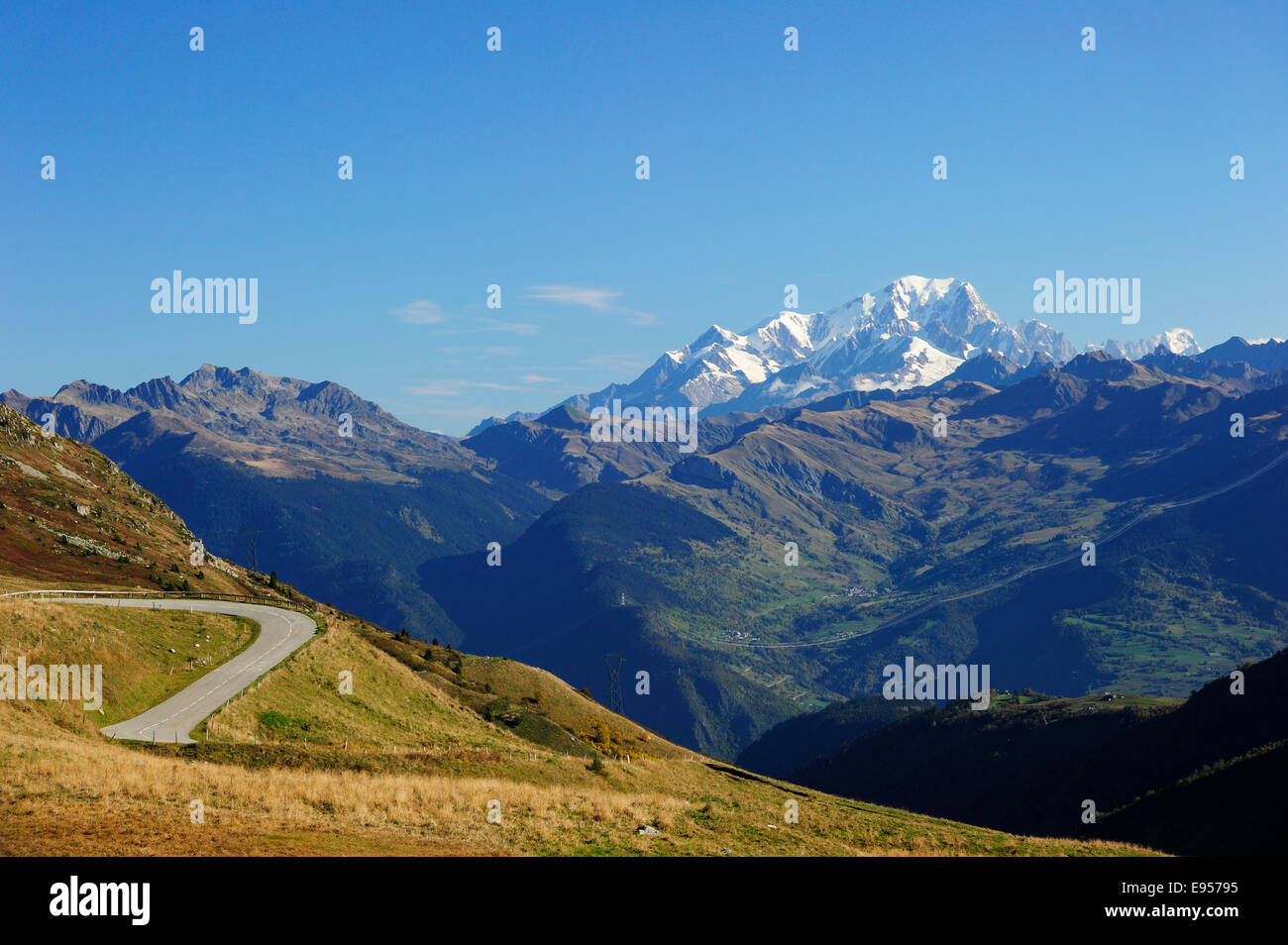 The pass road leading up to Col de la Madeleine, the snow-capped peaks of the Mont Blanc Massif at the back, Alps, Stock Photo