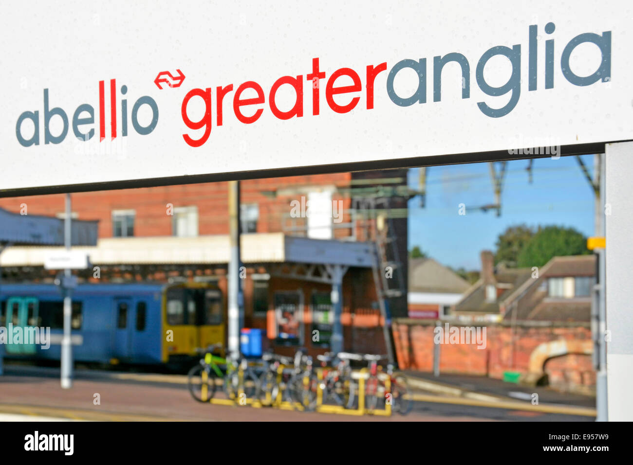 Abellio Greater Anglia brand name on railway station platform sign framing a Metro all stations train waiting to - Stock Image