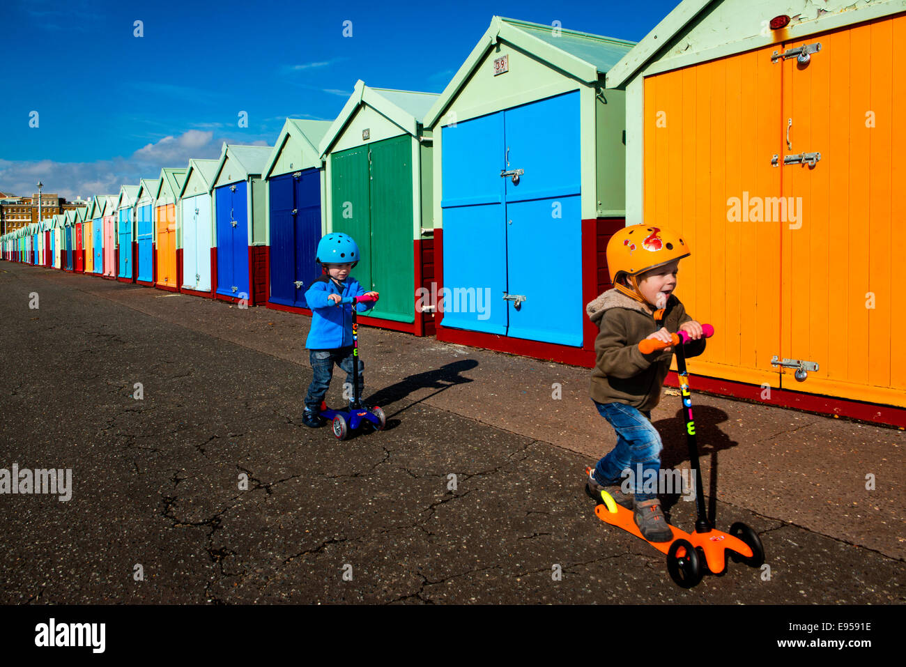 Twin boys on scooter at Brighton beach huts - Stock Image