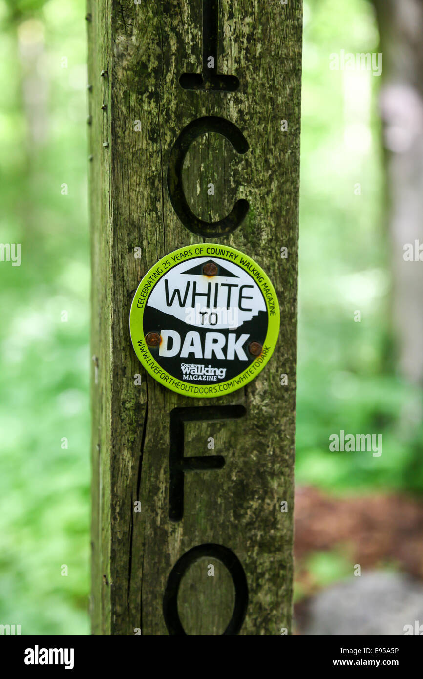 A sign disc on a public footpath post saying white to dark which is the footpath designed by Country Walking magazine - Stock Image