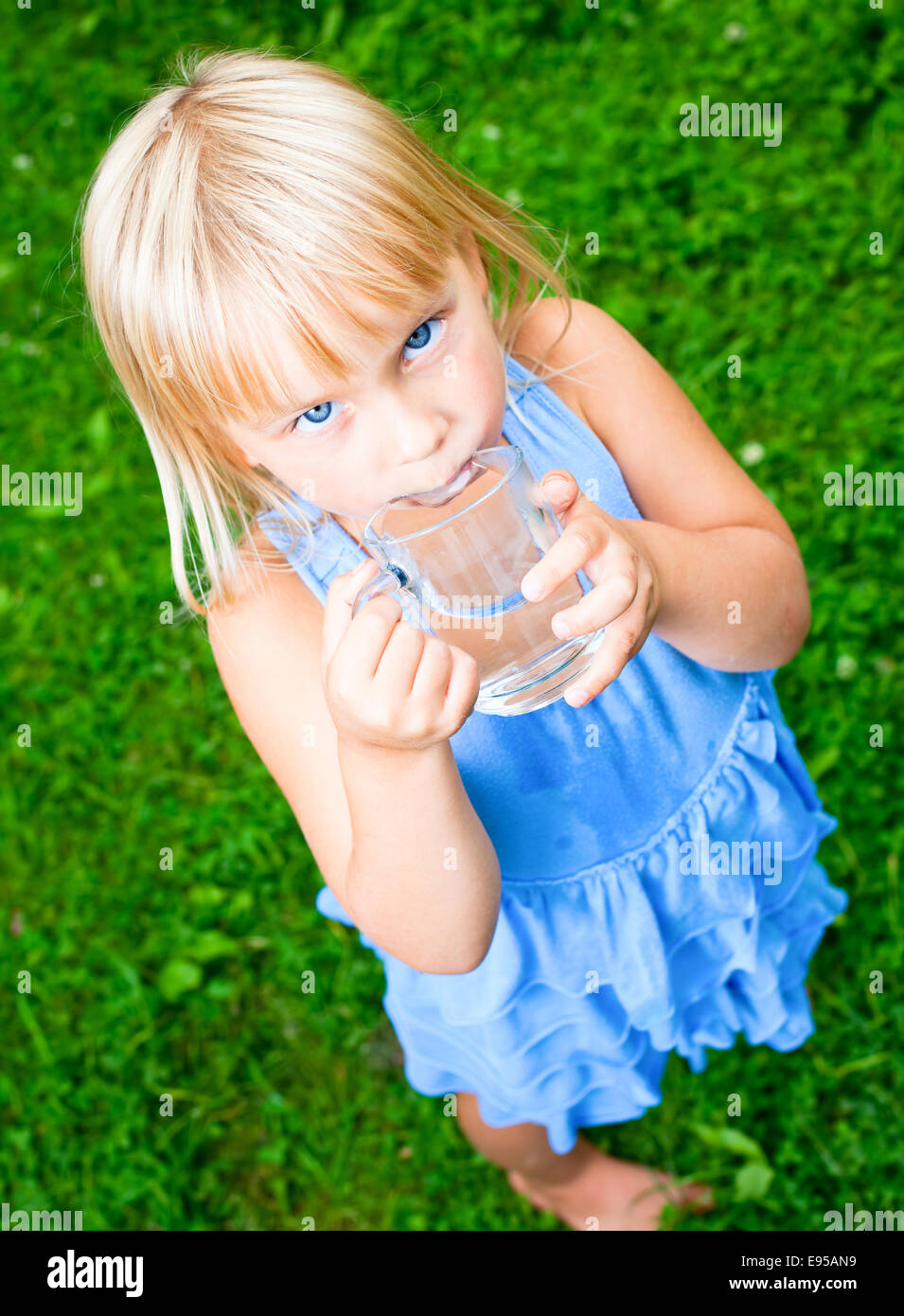Cute little girl drinking water outdoors - Stock Image