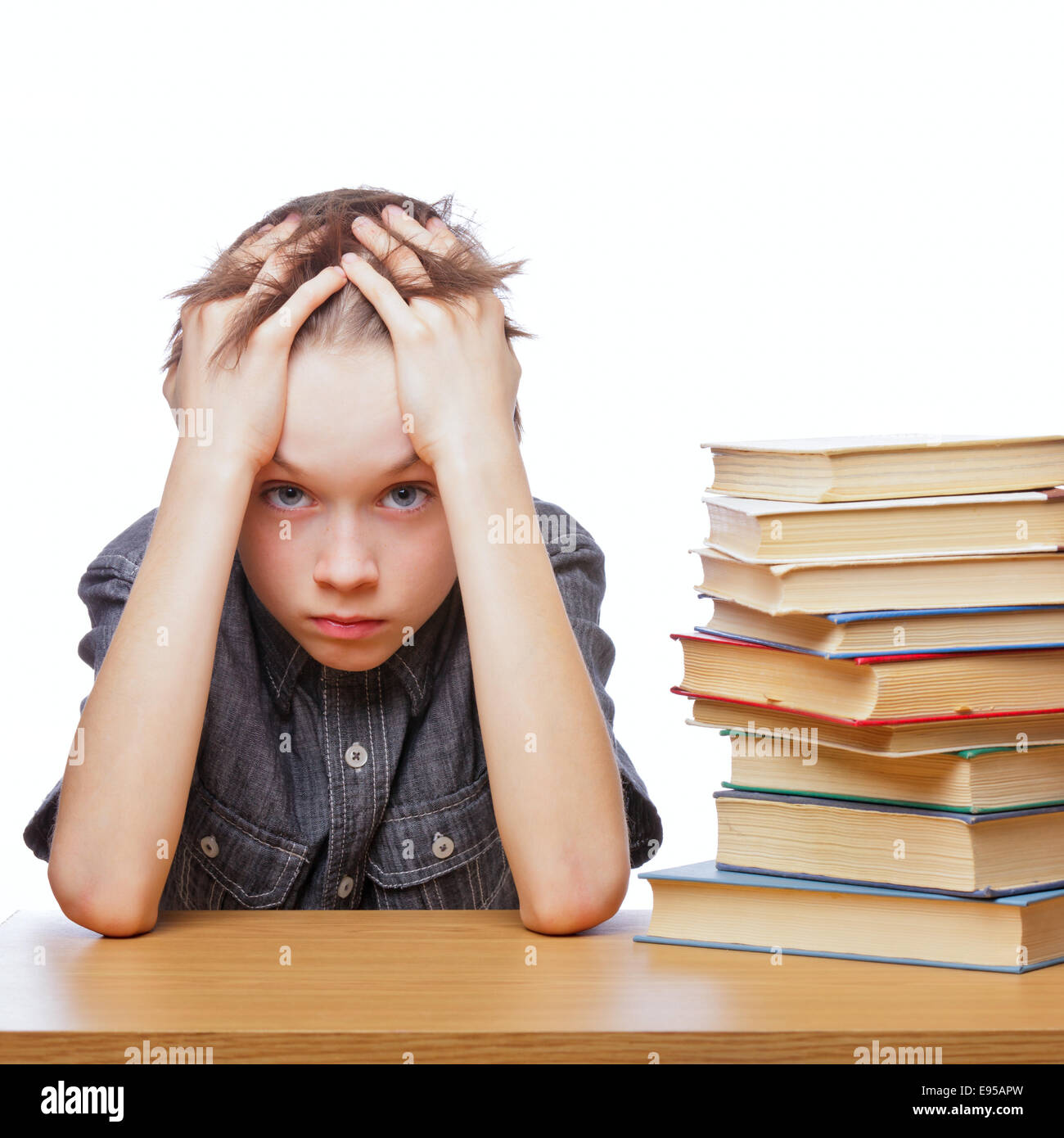 Portrait of upset schoolboy sitting at desk with books holding his head - Stock Image