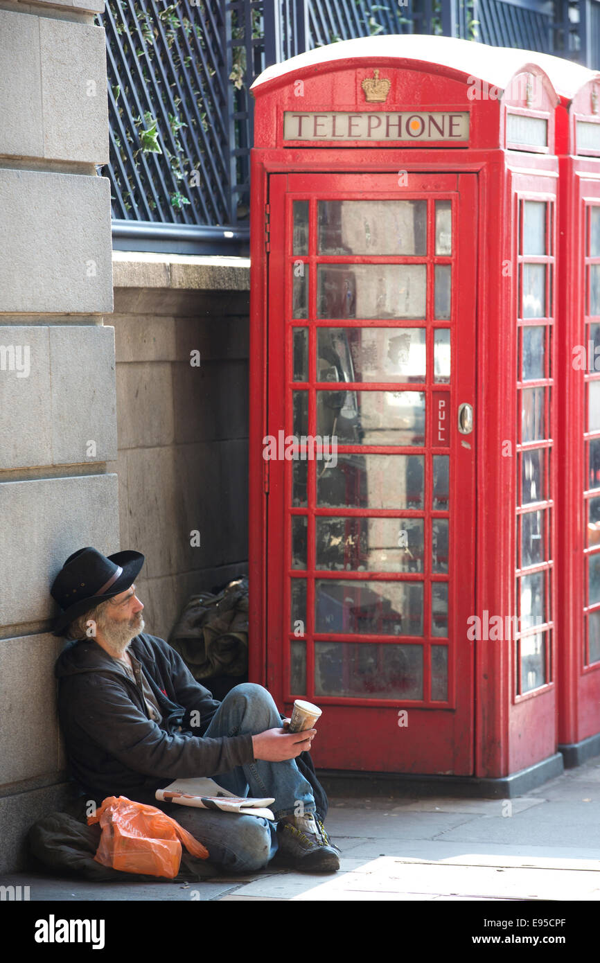 Homeless man begs for money, outside the Ritz hotel on Piccadilly, West End, London, England, UK - Stock Image