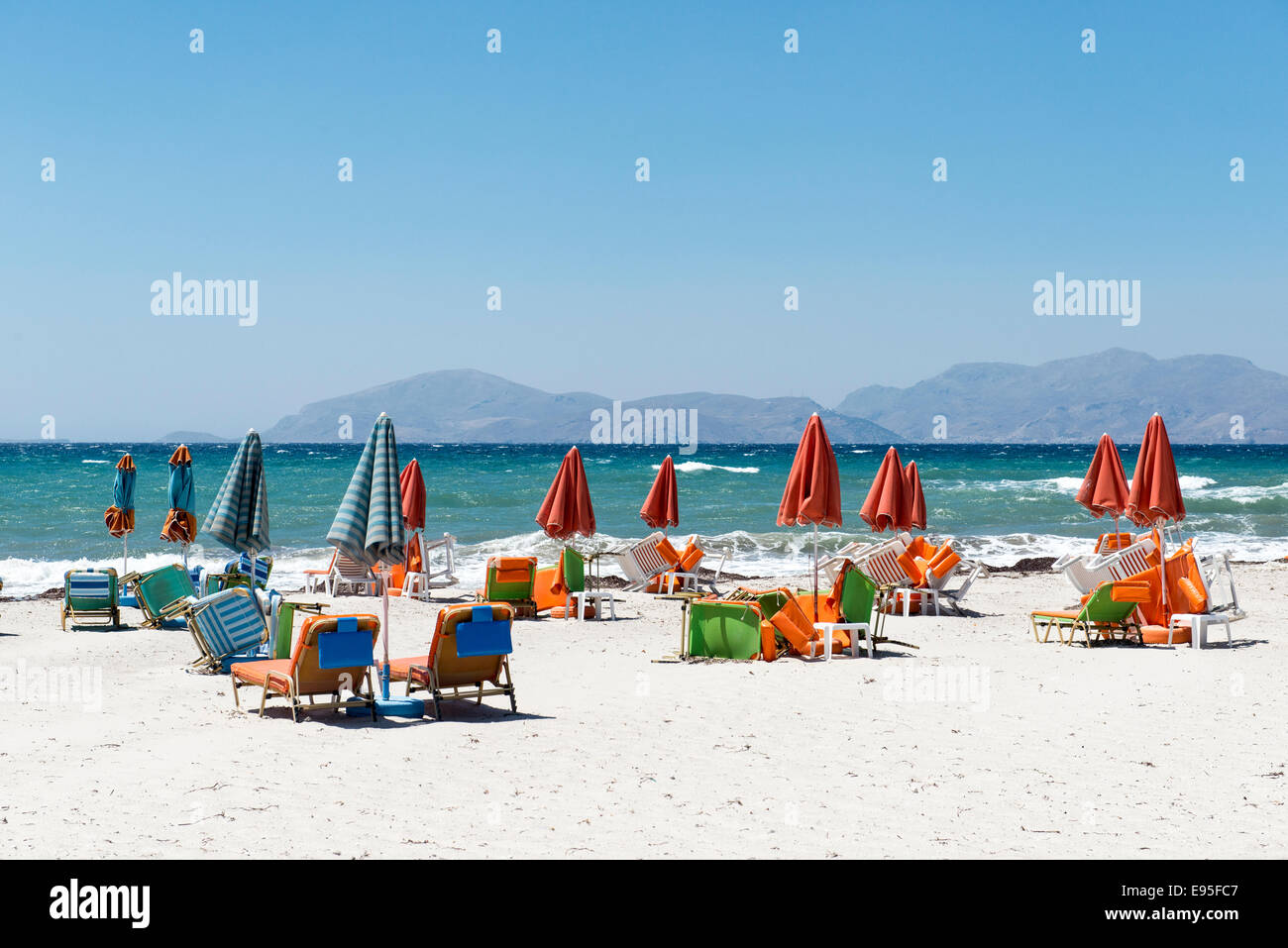 Empty beach with closed parasols and sun loungers on the beach of Mastichari, island of Kos, Greece - Stock Image