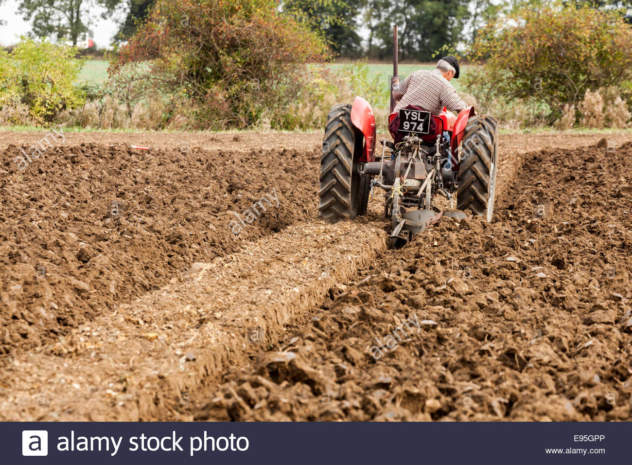 Old fashioned tractor ploughing a field - Stock Image