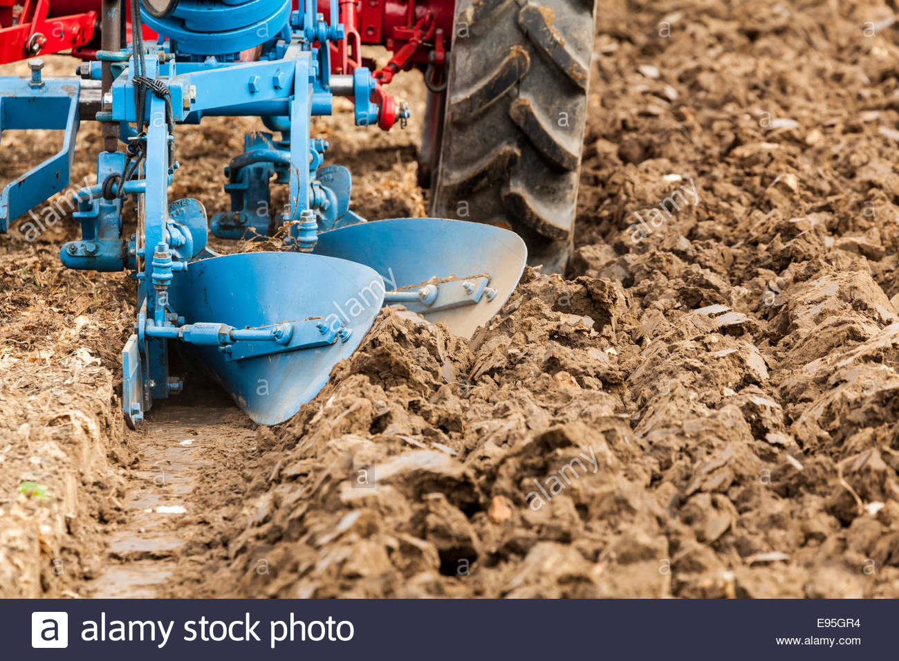 Close up of a tractor ploughing a field - Stock Image