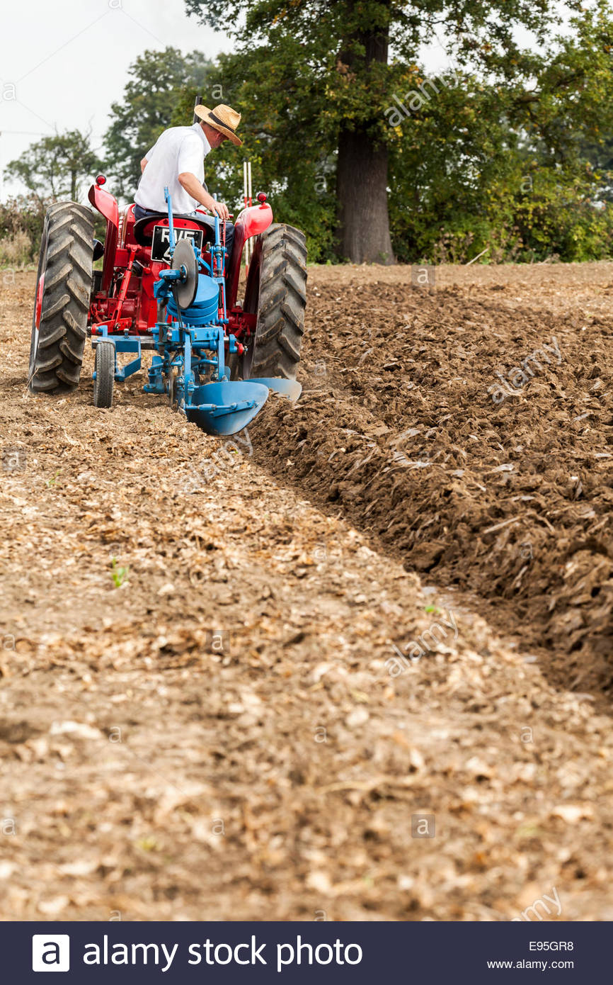 Old fashioned tractor ploughing field - Stock Image
