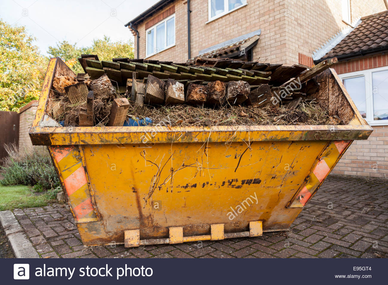 Large skip full of garden waste and fencing - Stock Image
