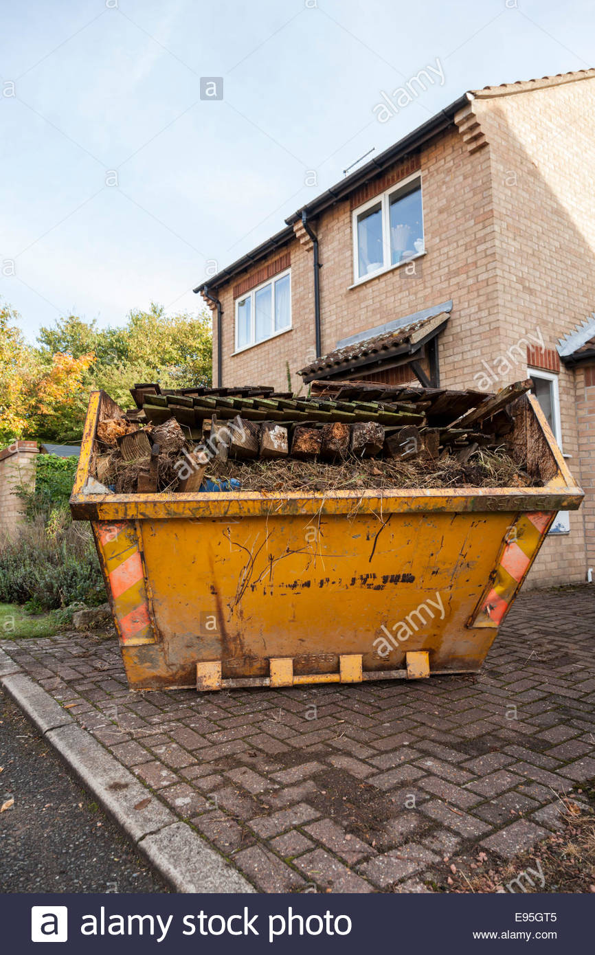 Skip full of garden rubbish on a driveway outside a house - Stock Image