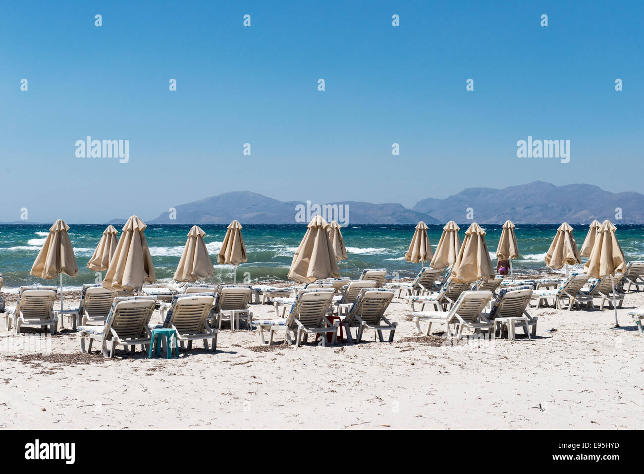 Empty beach with closed parasols and sun loungers on the beach of Mastichari, island of Kos, Greece Stock Photo