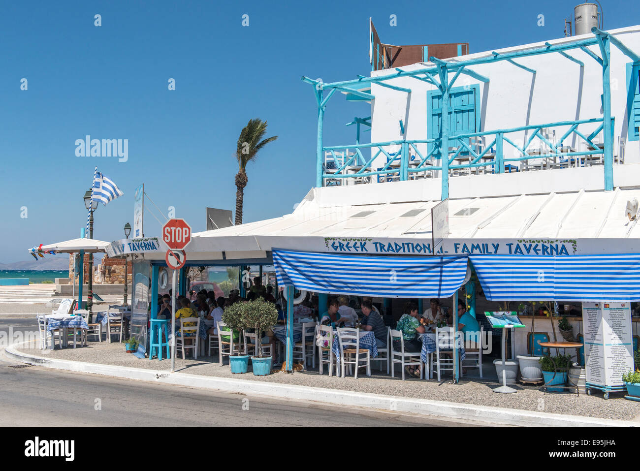Seafront tavern with guests dining, Mastichari, island of Kos, Greece - Stock Image