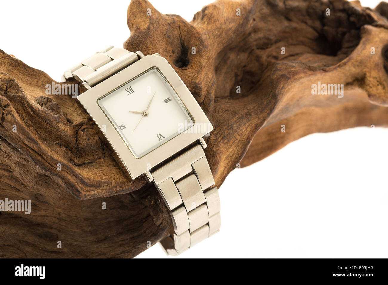 A mans wrist watch on a piece of fossilised wood - studio shot with a white background - Stock Image