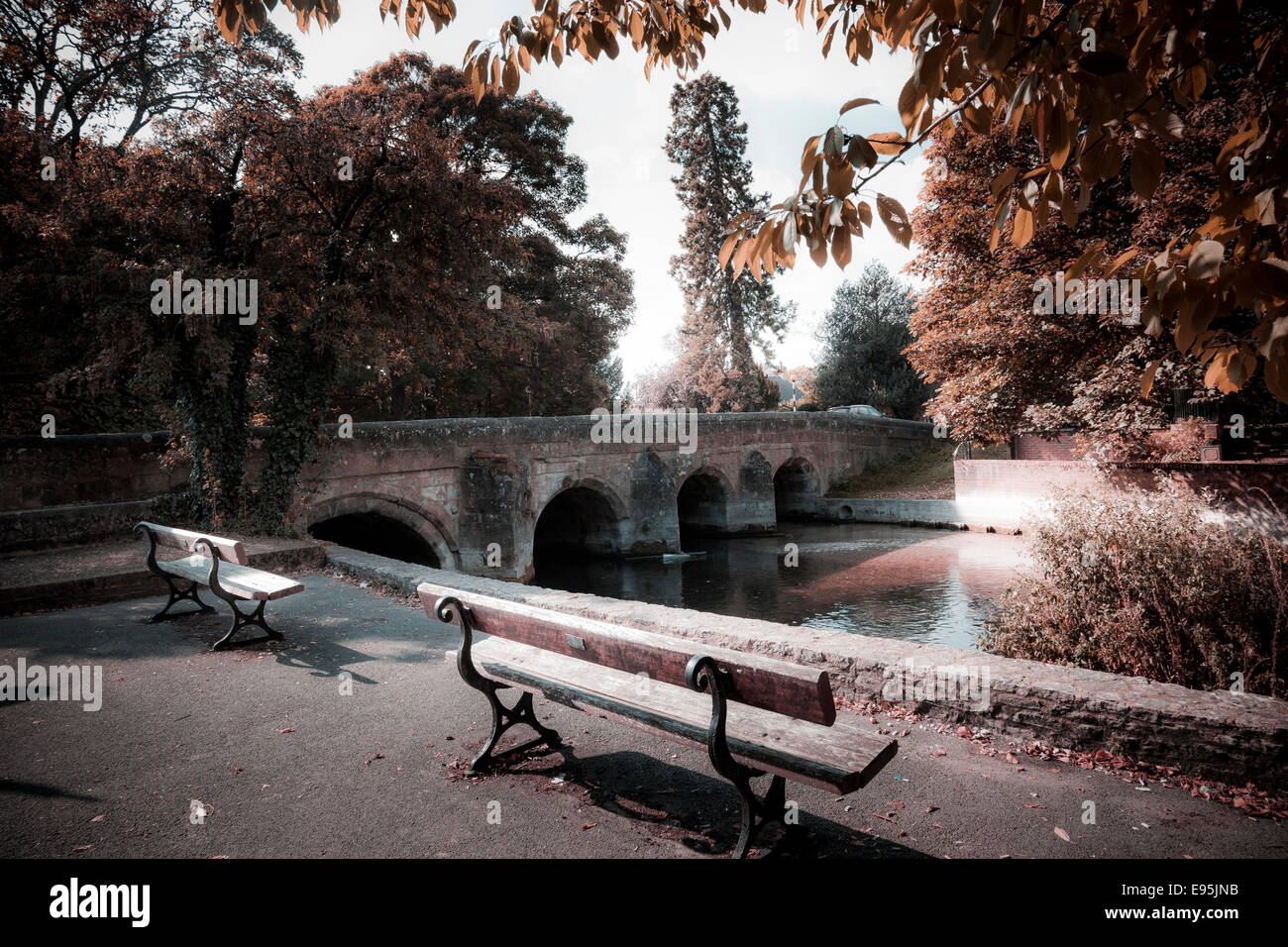Unoccupied benches by stone bridge over the River Avon processed for soft autumn colours - Stock Image