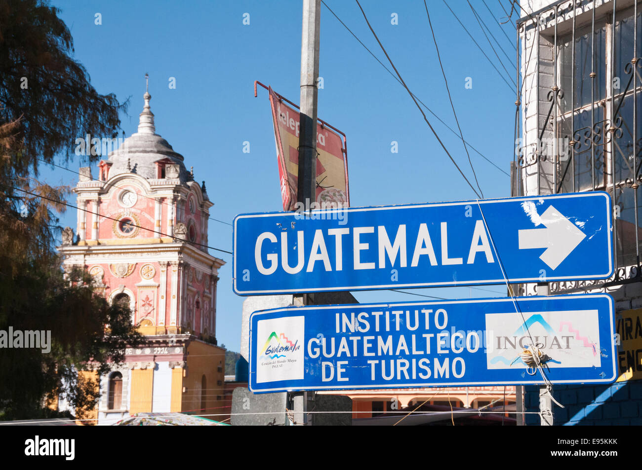 Road sign pointing to Guatemala City, with the City Hall Clock Tower behind, Solola, Guatemala - Stock Image