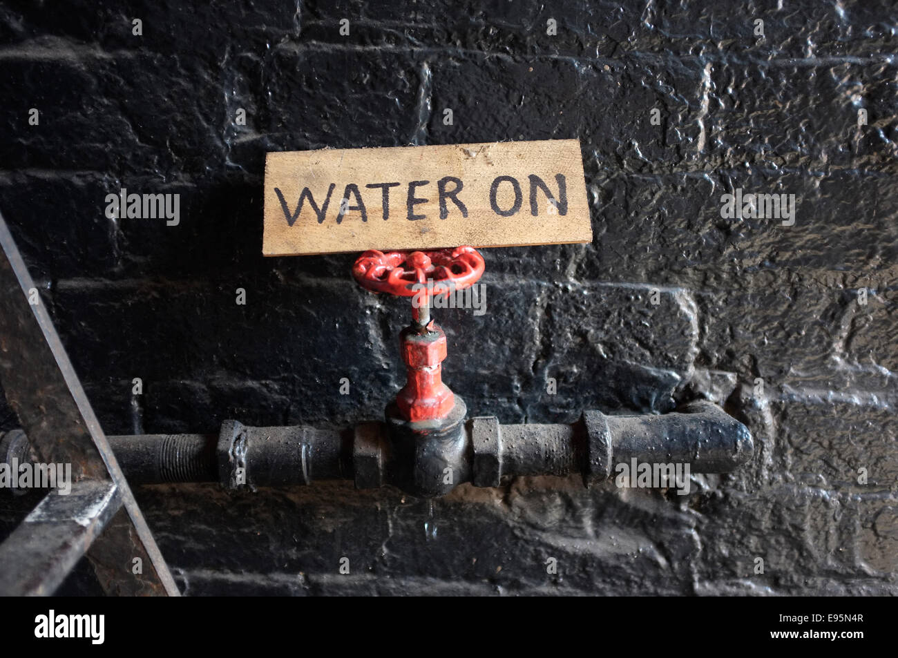 Red water tap with handwritten Water On wooden sign. - Stock Image