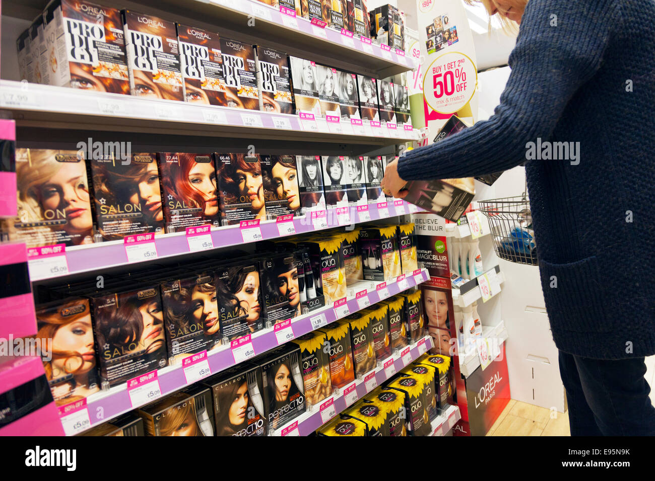 Woman shopping at Chemist shop store for hair dye product products inside browsing choosing lady female Stock Photo