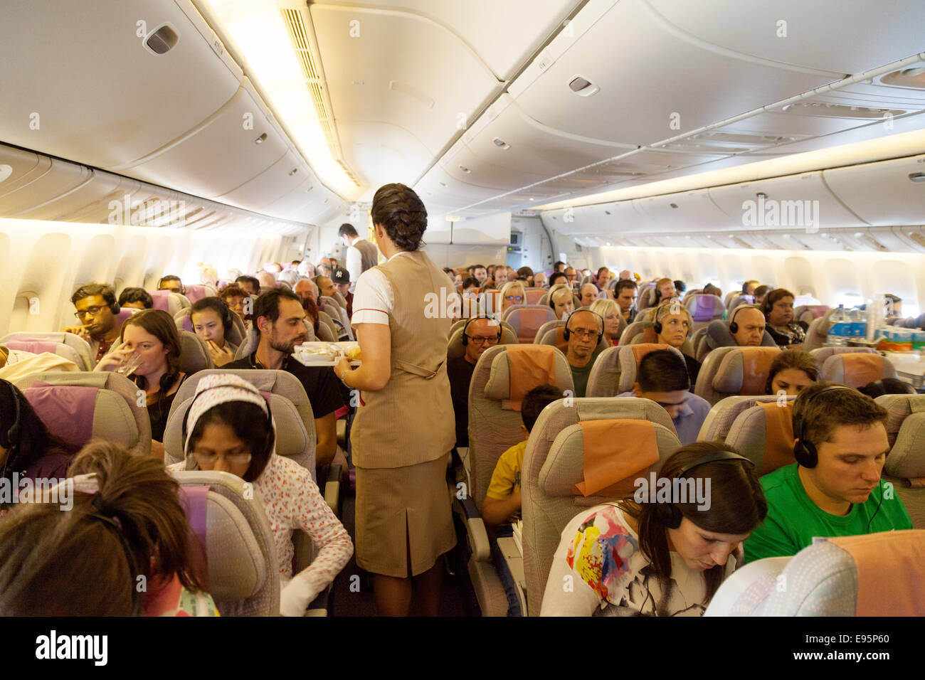 Passengers and stewardess on board an Emirates Airline plane; the cabin of a Boeing 777 flight from London to Dubai - Stock Image