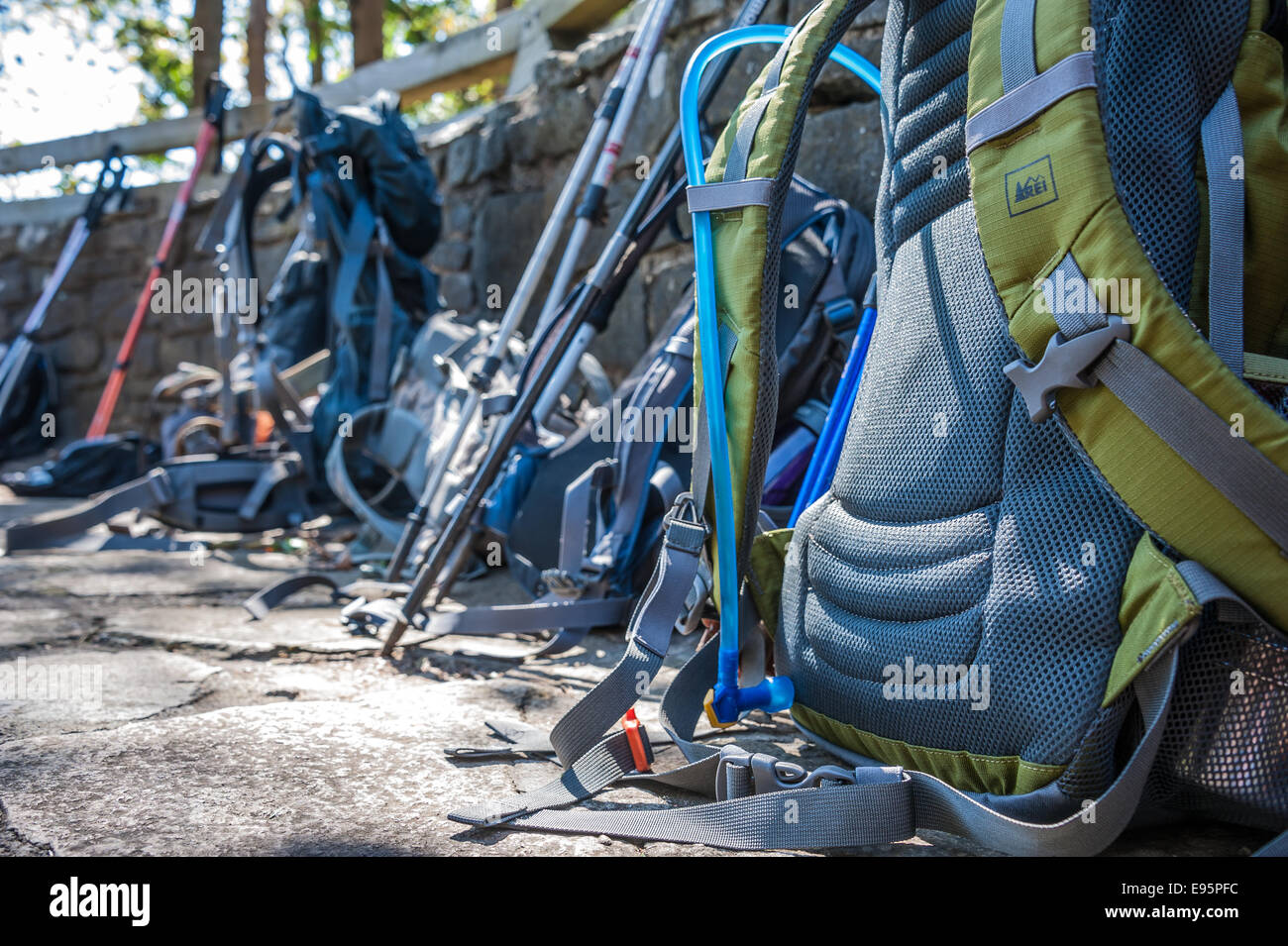 Hikers' backpacks and walking sticks line the stone wall of the overlook at Neels Gap on the Appalachian Trail - Stock Image