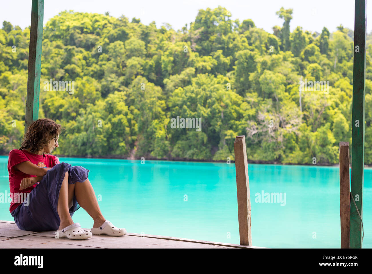 Tourist watching the stunning colors of the remote Togean Islands (or Togian Islands), Central Sulawesi, Indonesia. - Stock Image