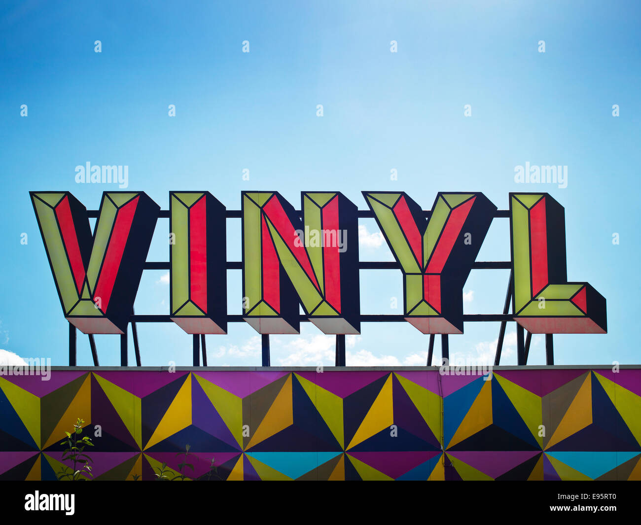 roof top sign depicting vinyl word / slogan with bright colours against blue sky above derelict club - Stock Image