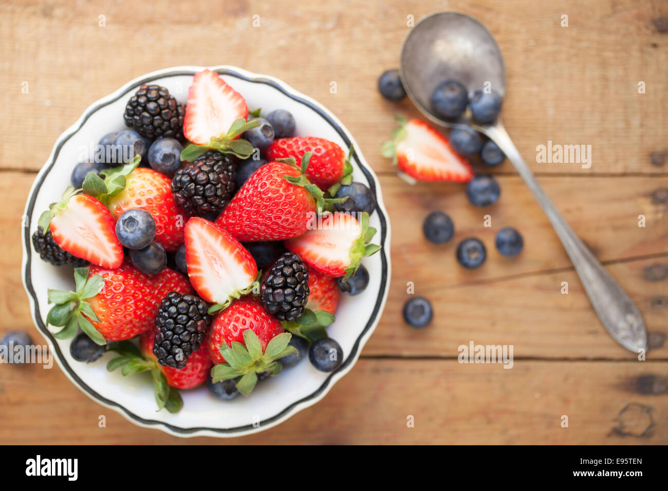 A bowl of mixed berries on a rough wooden table top. - Stock Image