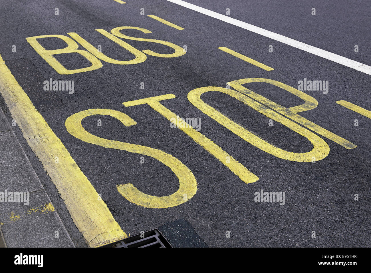 Bus Stop Painted onto a Tarmac Road, London, United Kingdom. - Stock Image