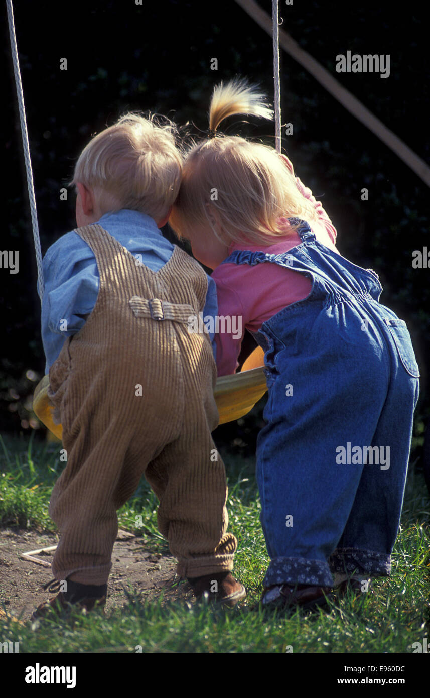 two toddlers from back pushing swing - Stock Image