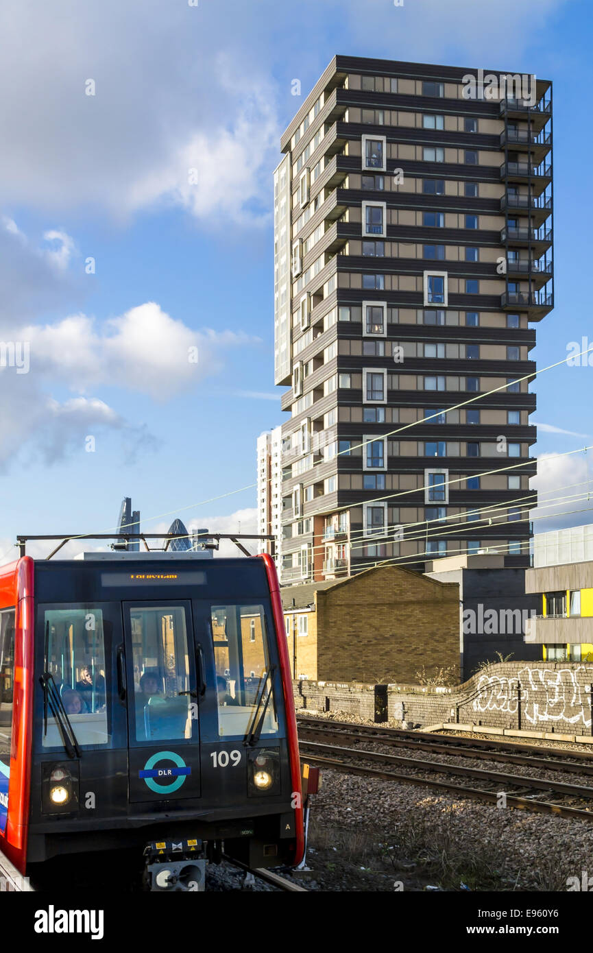 A Docklands Light Railway train passes a high rise block of social housing flats in Shadwell, East London, Tower Stock Photo