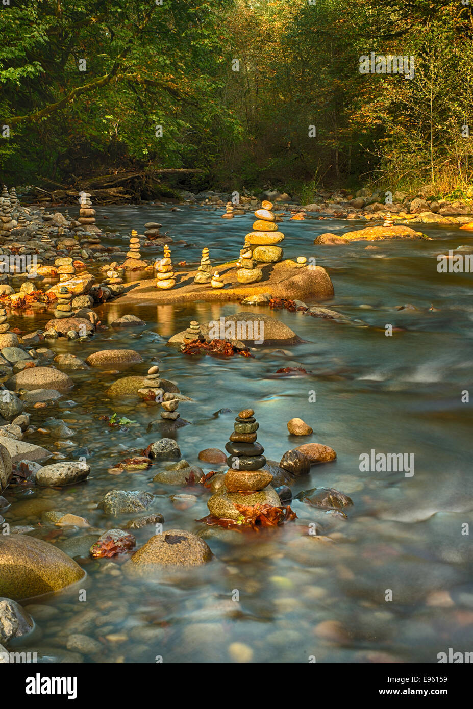 Stacked rock cairns in tranquil river with golden light - Stock Image