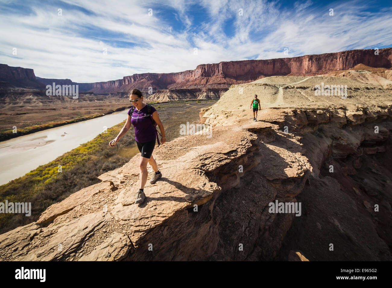 Hikers on the trail to Fort Bottom ruins from the White Rim trail near Moab, Utah. Canyonlands National Park. Stock Photo