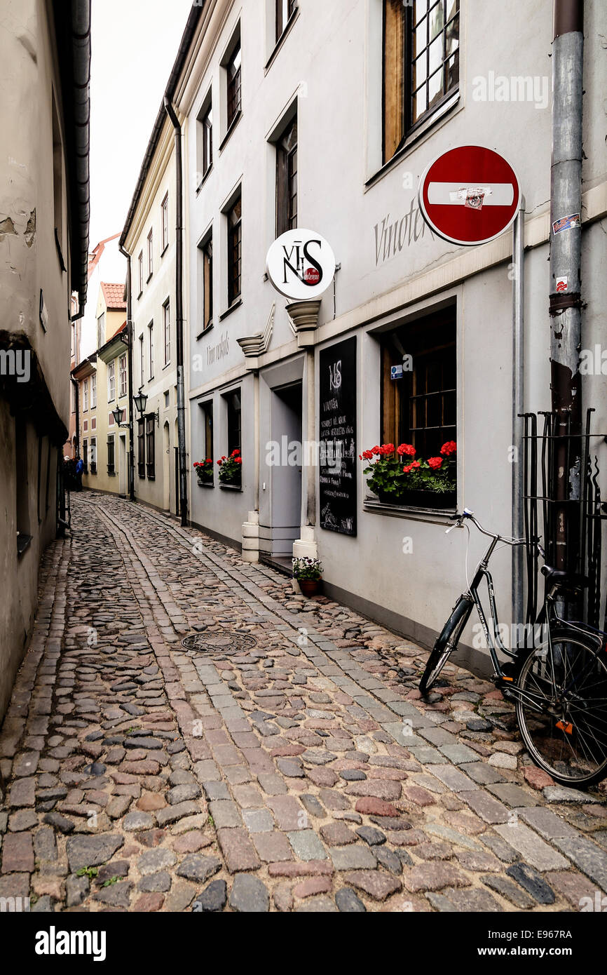 Bicycle leaning against wall in narrow street near a wine bar in historic old centre of Riga, Latvia - Stock Image