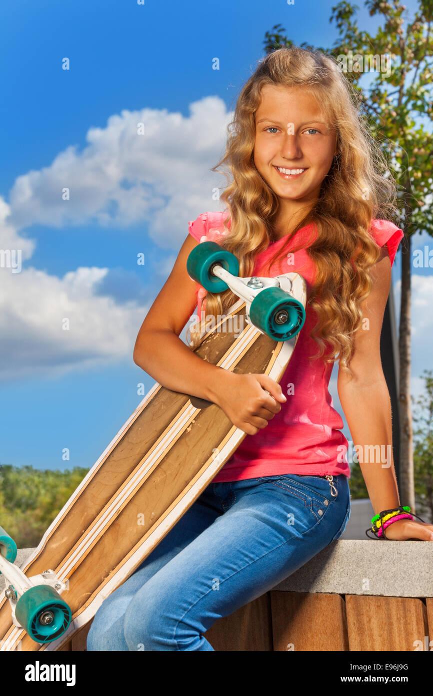 Positive girl holds skateboard sitting in park - Stock Image