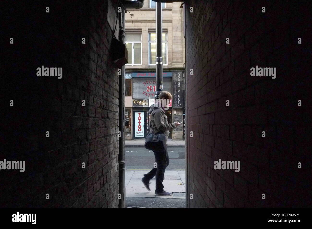 A man walks along Oldham Street , Manchester , reading his smartphone. - Stock Image