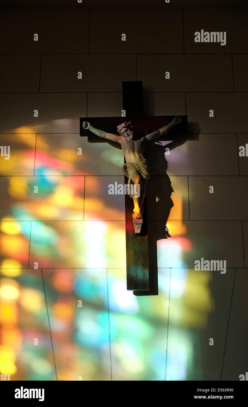 colorful stained glass window reflections on wall and crucifix - Stock Image