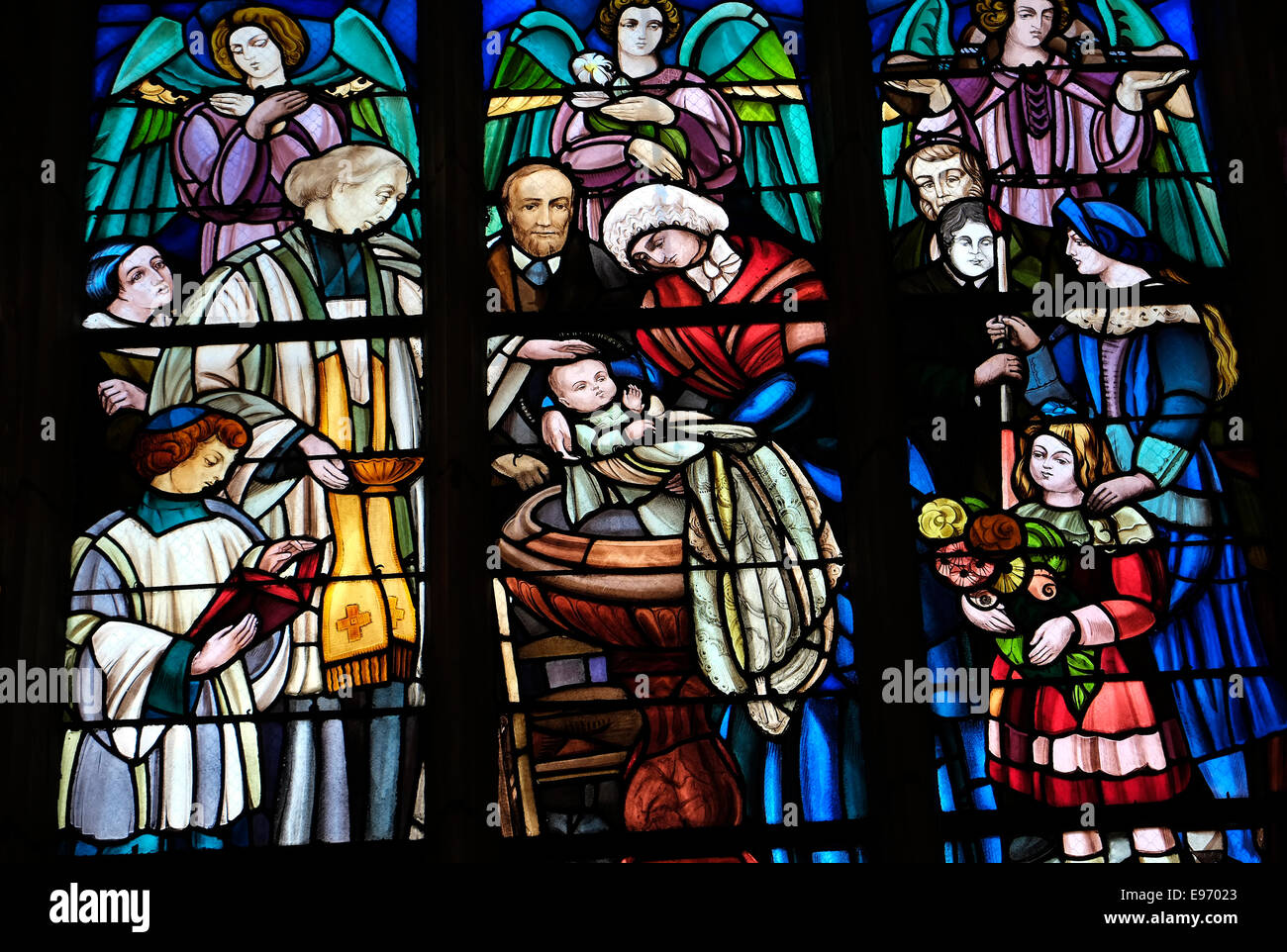 stained glass window depicting colourful baptism scene - Stock Image